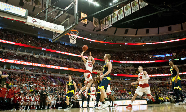 Bronson Koenig (24) drives to the basket against Michigan at the United Center. PHOTO: Bob Campbell